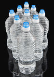 Water Bottles on Black. Water Bottles with blue cap on Black Background Royalty Free Stock Photo