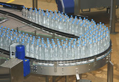 Water bottles on conveyor and water bottling machine ind Royalty Free Stock Photography