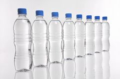 Water bottles in a line. Eight water bottles with blue lids in a row Stock Photos