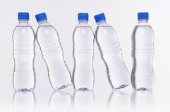Water bottles reflection. Row of five water bottles with reflection Stock Image