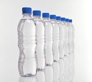Water bottles row. Row of eight water bottles disappearing into distance with focus on front bottles Royalty Free Stock Photos