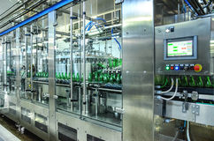Water bottling plant. Water green bottling plant. Industrial conveyor of mineral water. process equipment Stock Photography