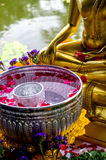 Water bowl in front of Buddha statue. A water bowl with flower petals sits in front of a Buddha statue to be used to cleanse the Buddha during Songkran festival Royalty Free Stock Photography