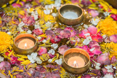 Water in bowl mixed with candle and flowers corolla for Songkran Royalty Free Stock Image