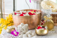 Water in bowl mixed with perfume and flowers. Stock Photos