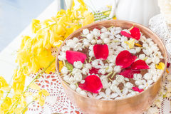 Water in bowl mixed with perfume and flowers. Royalty Free Stock Photos