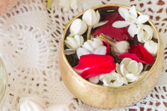 Water in bowl mixed with perfume and flowers. Stock Images