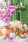 Water in bowl mixed with perfume and flowers. Royalty Free Stock Photo