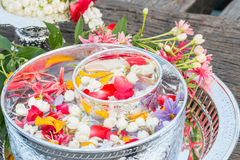 Water in bowl mixed with perfume and flowers. Stock Photo