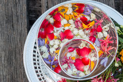 Water in bowl mixed with perfume and flowers Stock Photo