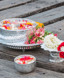 Water in bowl mixed with perfume and flowers Stock Images