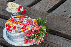Water in bowl mixed with perfume and flowers. Stock Photography
