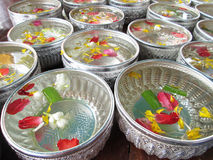Water in bowl mixed with perfume and vivid flowers corolla for Songkran festival in Thailand. Closeup Royalty Free Stock Image