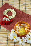 Water in bowl mixed with perfume and vivid flowers Royalty Free Stock Photos
