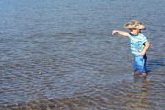 Water boy. Small boy throwing stones in the water Royalty Free Stock Photos