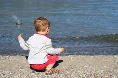 Water boy. Small boy throwing stones in the water Royalty Free Stock Image