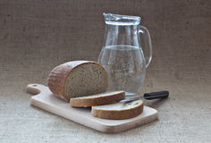 Water and bread. Slices of bread on breadboard with jar of water Stock Photos