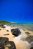 Water breaking over a rock at the sea. Side on a beautiful sandy beach scattered with rocks alongside an azure blue tropical ocean Royalty Free Stock Photos