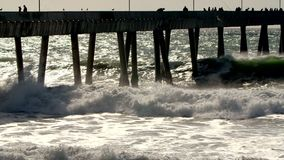 Water breaking on pier. Slow movement of ocean waves breaking against the pier, walked by people observing beautiful weather while the sun shimmers off the water stock footage