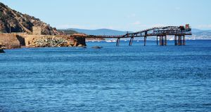 Rio Marina bridge, town, Elba island, card, Italy, swimming. Water, bridge, blue sea, rocks, waves and sea background, romantic landscape with sunrays on the royalty free stock photos