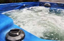 Spa Jacuzzi Hot tub bubbling water close up. Water bubbles in blue spa hot tub jacuzzi royalty free stock images