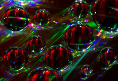 Water bubbles on compact disc surface. Abstract composition created by diffracting light on the wet surface of a compact disc Stock Photos