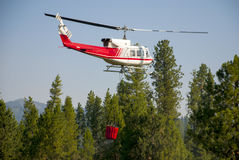 Water bucket carried by helicopter to a fire Stock Photography