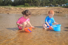 Water and bucket play at the beach. Young boy and girl playing in water at beach with buckets and spades Stock Photography