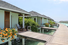 Water bungalow with flowers and log footbridge in the Maldives Stock Photo