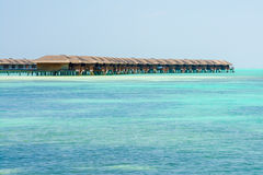 Water bungalows of an island resort extend into the lagoon in Ma Royalty Free Stock Photo