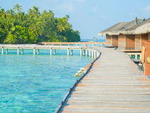 Water bungalows of an island resort extend into the lagoon in Ma Stock Photos