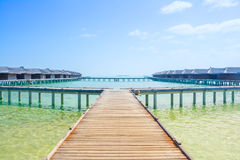 Water bungalows of an island resort extend into the lagoon in Ma Stock Photography