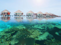 Water bungalows in a Maldives island resort with under water coral reefs Stock Images