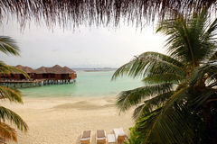 Water bungalows, ocean and sky in Maldives. View from beachfront cottage stock image