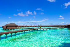 Water bungalows and wooden jetty on tropical Stock Images