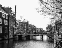 Water canal, aka gracht, and narrow houses along it in Amsterdam city centre, Netherlands, black and white image.  Stock Photo