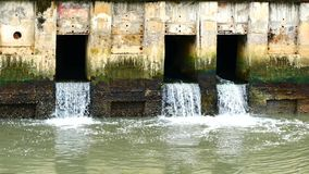 Water from a canal in the city is dropping down to the sea. To drain water and to prevent floodin. Daily life video After the rain. Water from a canal in the stock footage