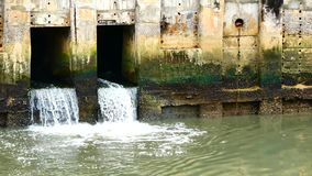 Water from a canal in the city is dropping down to the sea. To drain water and to prevent floodin. Daily life video After the rain. Water from a canal in the stock video footage