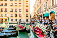 Water canal with gondolas in Venice. Venice, Italy - May 18, 2016: Gondoliers waiting for clients near crowded with tourists street. Sailing in godolas is a most Stock Photo