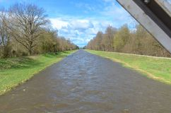 Water canal or river with green banks in spring stock photo