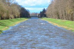 Water canal or river with green banks in spring stock photos