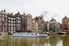 Water canal with sightseeing tourism boat in Amsterdam, Holland Stock Images