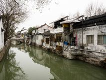 White walled houses reflected in canal waters in historic downtown Suzhou. Water canal in Suzhou old town lined with white walled houses Royalty Free Stock Photography