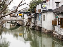 White walled houses reflected in canal waters in historic downtown Suzhou. Water canal in Suzhou old town lined with white walled houses Stock Images