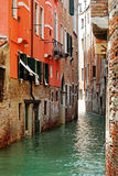 Water canal in Venice & old rustic stone buildings Royalty Free Stock Photo