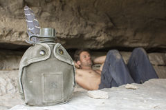 Water canteen and army man resting in cave stock photos
