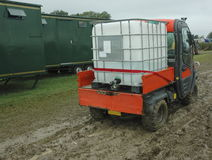 Water carrier vehicle. A vehicle loaded with huge container of water servicing mobile toilets at a very muddy and wet outdoor event Stock Photos