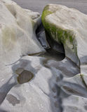 Water carved rocks. Wave action carves patterns into the rocks along a sandy beach at Olympic National Park, Washington Royalty Free Stock Image