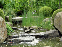 Water cascade. Water flowing from rocks at a garden conveying a peaceful, tranquil and calming feeling or mood royalty free stock photo