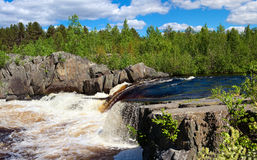 Water cascade between the grey rocks. In summer season. Blue sky with clouds. Pines on the stones. Karelia, Russia Stock Photos